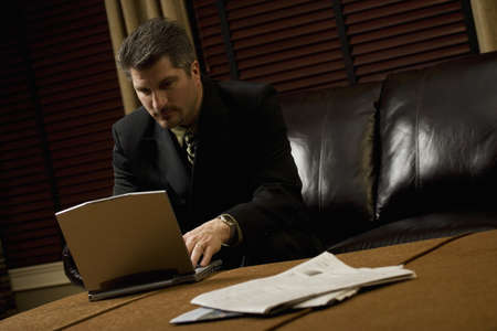 fortysomething: Businessman working on his laptop on the coffee table