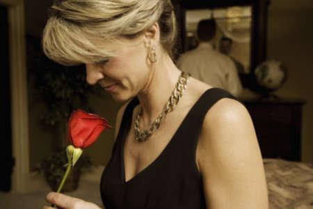 Vrouw ruiken een rode roos  Stockfoto