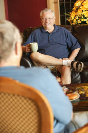 seventy something: Senior man sitting and visiting with other senior man