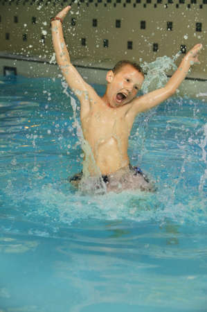 indoors: Boy splashing in a pool Stock Photo