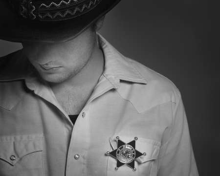 leah: Cowboy looking down under hat with Sheriffs badge on shirt