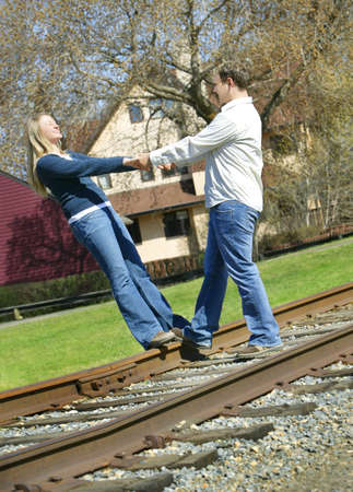 Couple holding hands on railroad track photo