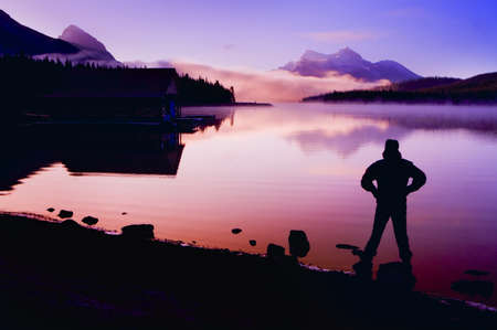lac montagne: Silhouette of a man at a mountain lake   Banque d'images