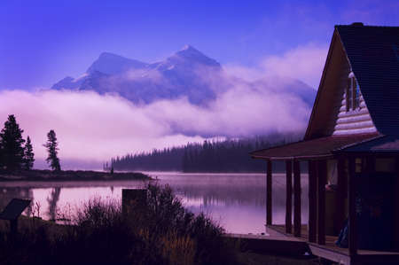 tranquillity: Cabin boathouse and foggy sunrise over mountain lake