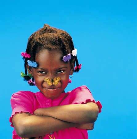 African little girl with arms crossed and a butterfly on her nose