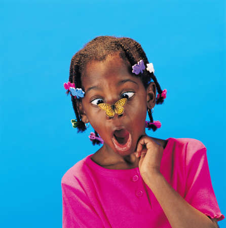 silliness: African little girl with butterfly barrettes and a butterfly on her nose looking surprised