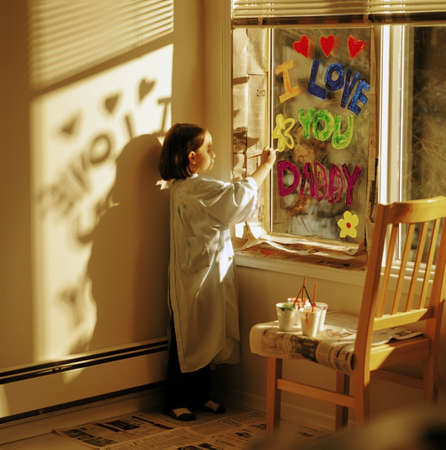 imaginative: Little girl painting I love you daddy on window Stock Photo