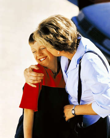 50 something fifty something: Mother kissing son on cheek Stock Photo