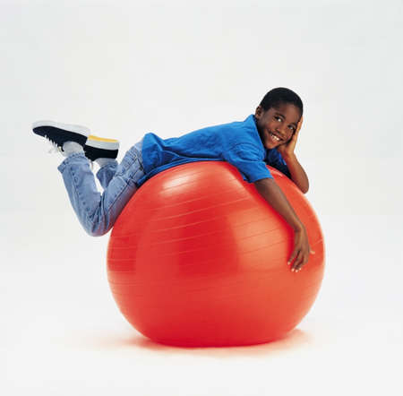 indoors: Young boy laying on large red ball Stock Photo