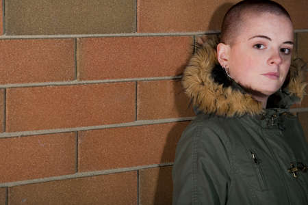 withdrawn: Teen girl with shaved head standing against brick wall