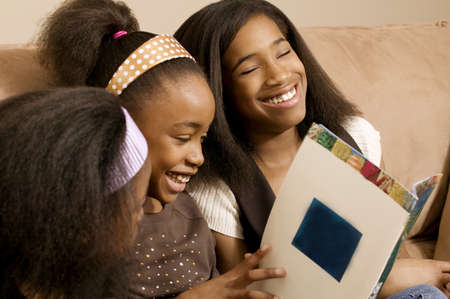 Girls reading and laughing together