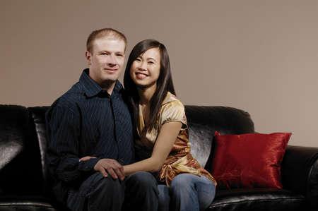 interracial marriage: Couple sitting chiudere sul divano  Archivio Fotografico