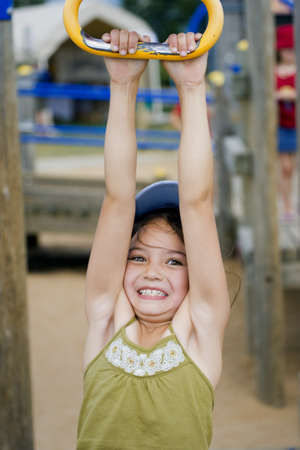 elated: Girl hanging from playground ride