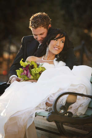 Newly married couple sitting on a bench