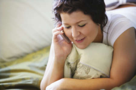 Woman using mobile phone on bed Stock Photo - 7200453