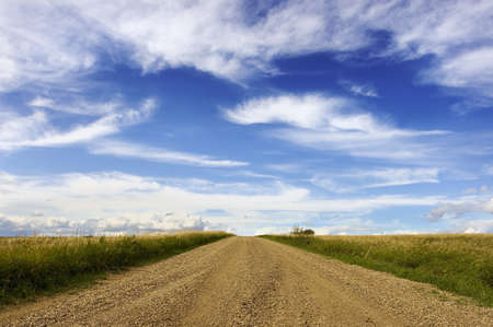 dusty: Gravel road with fields and white clouds