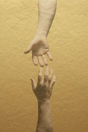 Two hands reaching with yellow wall