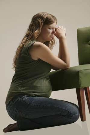fearful: Side view of a pensive pregnant woman sitting by chair