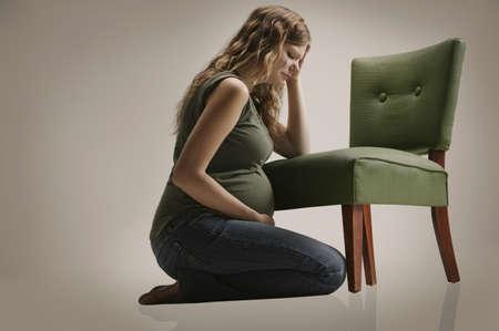 Una mujer embarazada triste sentado en silla  Foto de archivo - 7200552