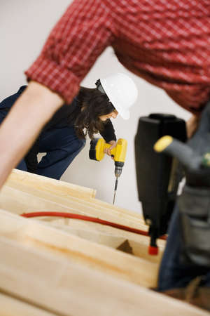 30 something women: Carpenters working with electric tools Stock Photo