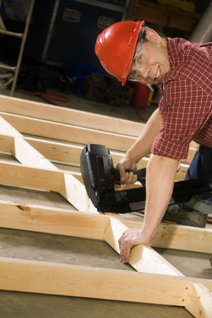 30 something: Content carpenter working with power tool Stock Photo