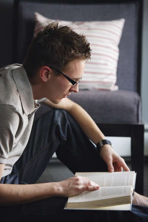 bookish: Young man sitting on floor reading a book