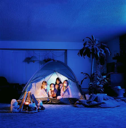 indoors: Children holding torches in a tent
