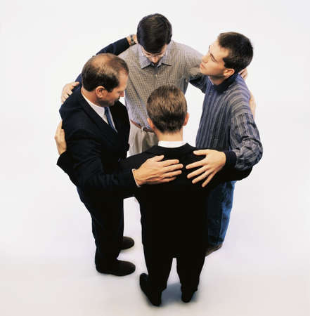 companion: High angle view of men praying and standing in a circle