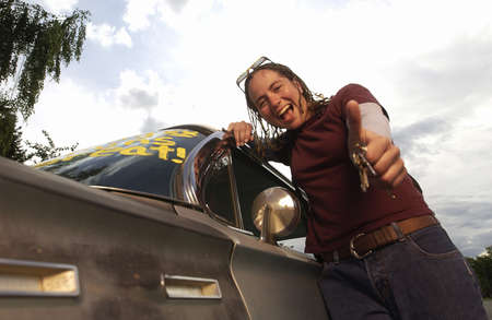 elation: Low angle view of a girl giving thumbs up while leaning on car