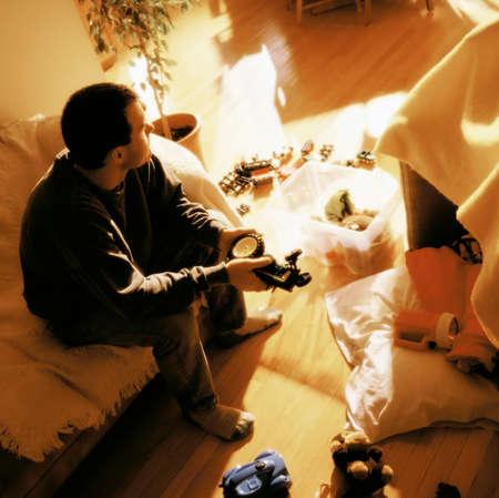 habitacion desordenada: Hombre rodeado de juguetes Foto de archivo