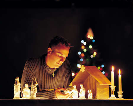 advent time: Man with nativity scene figurines and lights