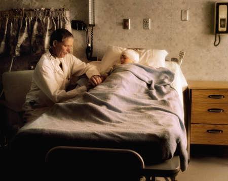 Doctor controle over een kind in een zieken huis kamer  Stockfoto