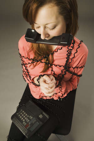 Woman bound by telephone cord photo