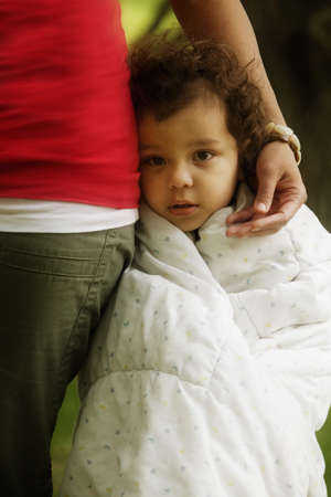 eyecontact: Child wrapped up in blanket at mothers side