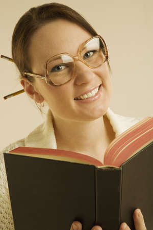 bookish: Woman smiling and reading book Stock Photo