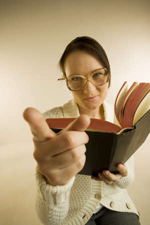 A woman holding book and pointing to the camera Imagens