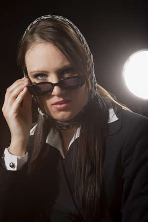 A young woman peering over sunglasses photo