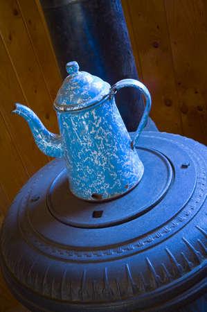 Antique coffee pot on pot belly wood stove   版權商用圖片