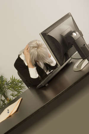 Woman sitting with head down in office Stock Photo - 7200411