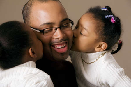 family unit: Girls kissing daddy on the cheek Stock Photo