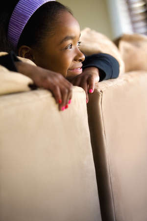 Girl looking over the back of couch Stock Photo - 7201113