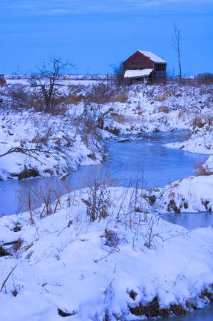 Abandoned shack near frozen creek in winter Reklamní fotografie