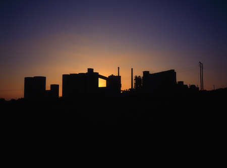 Concrete factory silhouette, backlit by the sun on the horizon