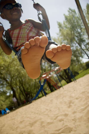 barefeet: Young girl on a swing in the park