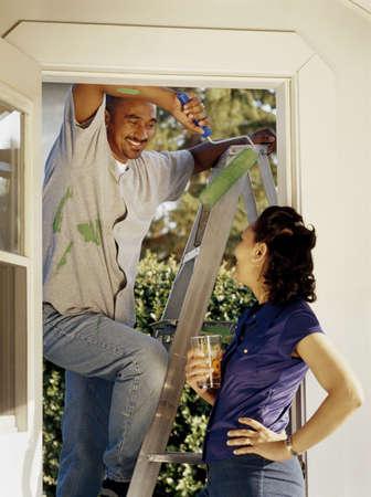 domestic chore: Hombre tomando un descanso de la pintura a la parte exterior de su casa