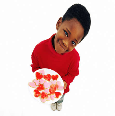 Boy holding plate of heart cookies Stock Photo