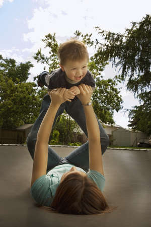 mums: Mother playing with son on trampoline Stock Photo