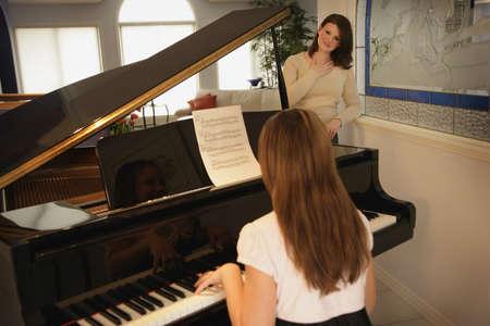 10 代の娘が彼女の母のピアノ 写真素材