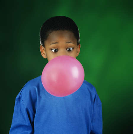 half length posed: Boy blowing huge bubble with bubble gum