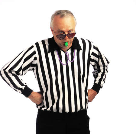 Referee with hands on hips blowing a whistle photo